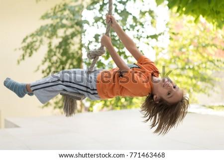 Cute happy little boy upside down on swing rope