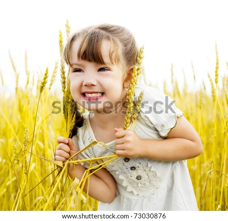 cute happy little girl in the wheat field