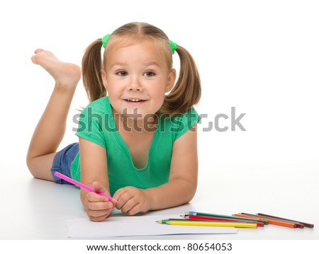 Cute happy little girl is drawing while laying on the floor, isolated over white