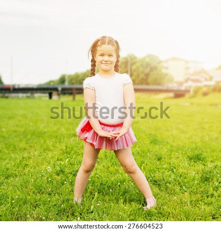 Cute happy little girl wearing tutu in park in summer. Beautiful five year old blonde girl with braids posing in park on sunny summer day. Retouched, natural light, square format.