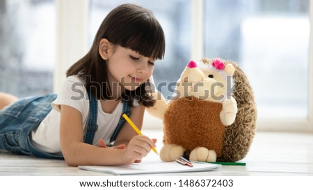 Photo of Cute happy little kid girl playing drawing pencils with fluffy hedgehog lying on warm heated floor at home, funny creative preschool small child teaching stuffed toy coloring picture having fun alone