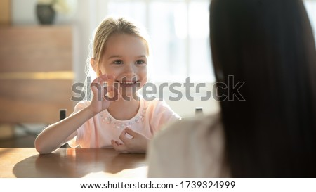 Cute happy little preschooler girl child make hand gesture learning sign language with mom or nanny, smiling small disabled kid practice nonverbal talk have lesson with teacher or tutor at home