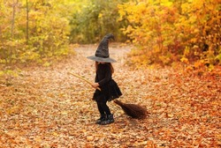 Cute happy little redhaired girl dressed in witch costume sitting on broom over autumn forest background with copy space, holding her hat with hands. Holiday of halloween celebration concept