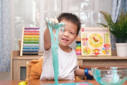 Cute happy smiling Asian 4 years old Kindergarten school boy having fun making fluffy slime, Young kid having fun playing and being creative by science experiment homemade toy called Slime