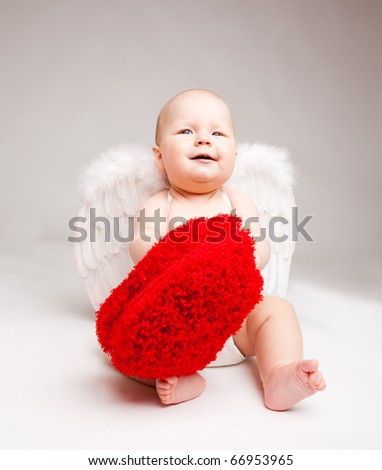 Cute happy valentine angel playing with fluffy heart, over gray