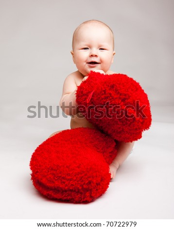 Cute happy valentine baby playing with red heart shaped pillows