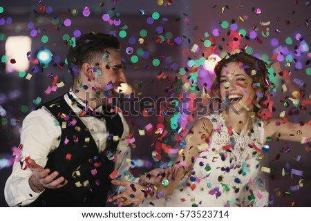 Cute happy wedding couple against defocused lights