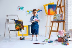 Cute, happy, white boy in blue shirt and jeans smiling and showing his colorful drawings. Little child having fun in artist studio. Concept of early childhood education, happy family, parenting