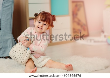 cute happy 2 years old baby girl playing with toys at home. Modern nursery interior in pastele tones, early learning concept