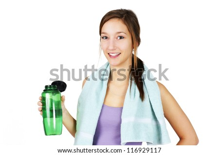 Cute, healthy and sporty young woman with towel on shoulders drinking water after working out, yoga or other exercise.