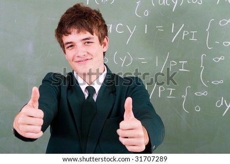 cute high school student in front of blackboard in classroom