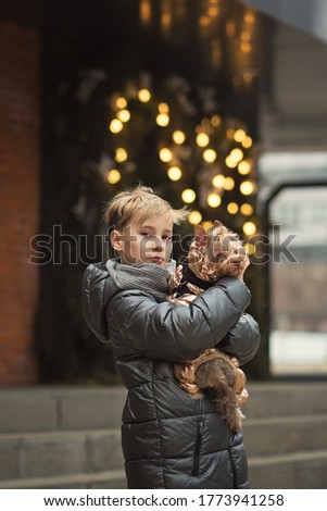 Cute hipster boy walks with her funny terrier. Little dog with young guy spend a day outdoors playing and having fun. Lifestyle portrait. Love between pet and owner. Soft focus