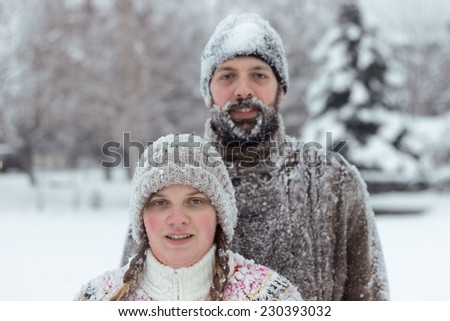 Cute hipster couple covered in snow, enjoying winter vacation