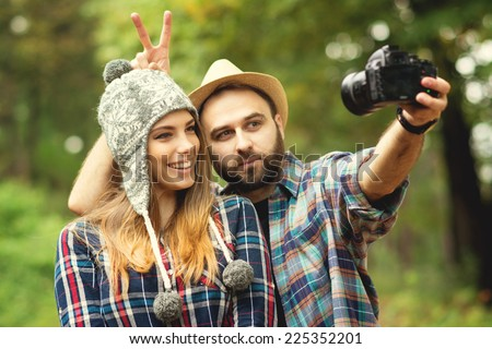 Cute hipster couple with hats taking a selfie with dslr camera in park in autumn. Closeup of young attractive blonde woman and bearded man posing for a self portrait outdoors.
