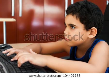 Cute hispanic  boy doing his homework on a computer at home