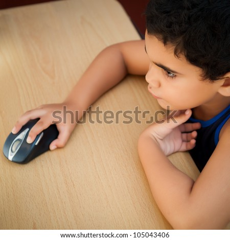Cute hispanic boy working with a computer on his bedroom at night (pictured from above)
