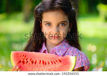Cute hispanic girl eating watermelon at park - stock photo