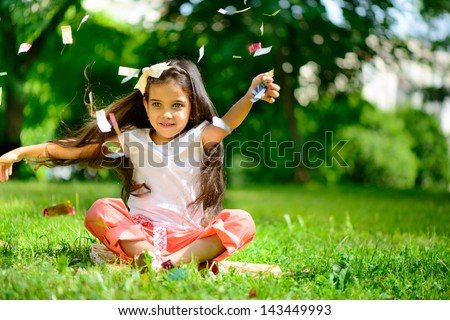 Cute hispanic girl throwing confetti at park