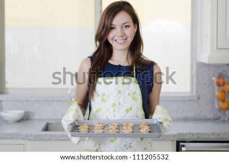 Cute hispanic housewife baking cookies