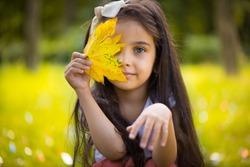 Cute hispanic little girl  hiding over yellow leaf
