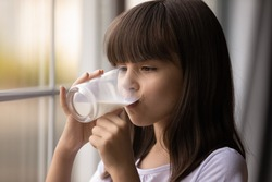Cute Hispanic little teen girl enjoy tasty delicious healthy dairy drink from glass at home. Small 9s kid child feel hungry thirsty drink wholegrain lactose-free soy yoghurt or milk. Health concept.