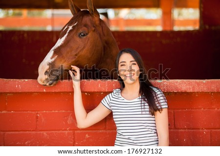 Cute Hispanic woman spending some time with a horse at the stables