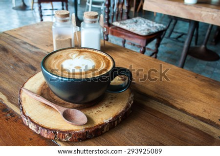 Cute Hot Latte Coffee on wooden saucer in cafe