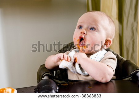 Cute hungry six month old baby eating solid food #38363833
