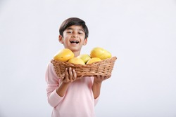 Cute indian/Asian little boy holding Mango basket in hand and giving multiple expressions. isolated over white background