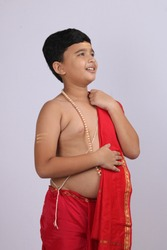 cute Indian boy in ethnic wear sovla and uparna - dhoti and stole. holding his stole.