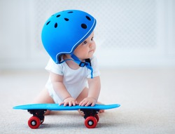 cute infant baby girl in protective helmet outfit ready to ride skateboard, extreme sport concept