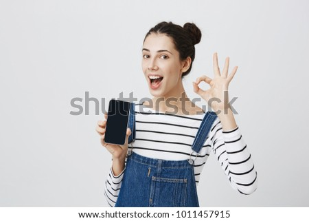 Cute joyful smiling young beautiful female holds modern smart phone, demonstrates it, has joy as uses it, shows ok sign, isolated against gray background. Body language and advertisement concept #1011457915