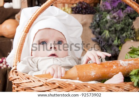 Cute kid as a chef sitting in the basket - stock photo