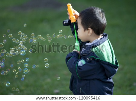 Cute kid blowing bubbles outdoors, in the forest in a beautiful sunny afternoon