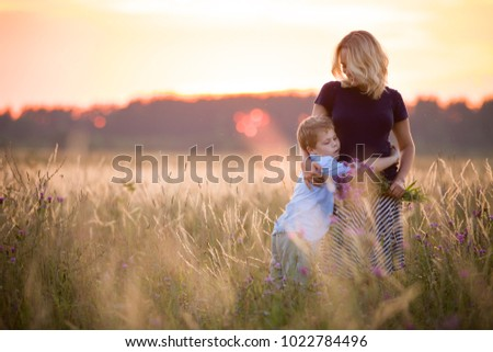 Cute kid boy hugging his mother on a summer meadow on beautiful summer sunset. Happy family together. Mum and child. Motherhood and childhood. Family walking in the field. Outdoors. #1022784496