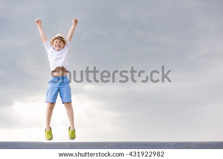 Cute kid boy jumping into cloudy sky - happiness, childhood, freedom, lifestyle concept - smiling boy in straw hat jumping in air over grey rainy sky. #431922982