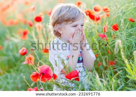 Cute kid boy laughing on poppy field on warm summer day. Warm evening light.