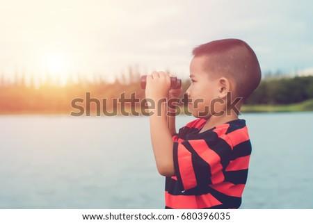 Cute kid boy standing on Riverside  and looking in spyglass. #680396035