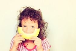 cute kid eating melon. filtered image.