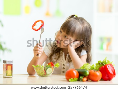 Cute kid girl not wanting to eat healthy food at kitchen
