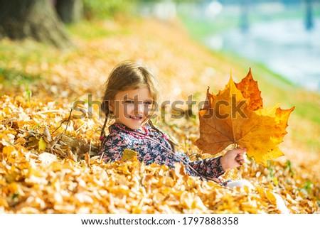 Cute kid girl woman in autumn park. Leaves falling. Autumn child mood