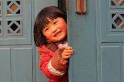 Cute kid hiding behind the door and peeking