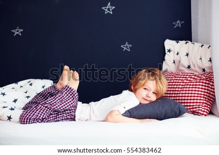 cute kid in pajamas lying in bed #554383462