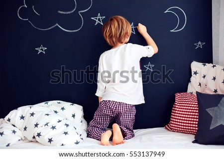 cute kid in pajamas painting chalkboard wall in his bedroom. #553137949