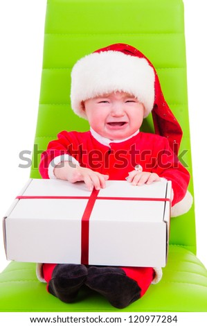 cute kid in Santa Claus clothes. sitting on a green chair and holding a big gift box