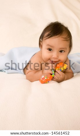 cute kid lying down on his tummy on blanket with stuck out tongue