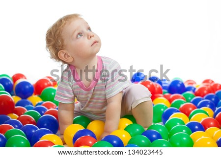 Cute kid or child playing colorful balls looking up