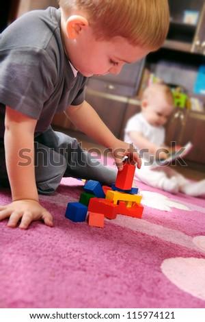 Cute kid playing with colorful cubes on the floor. His sister on background.
