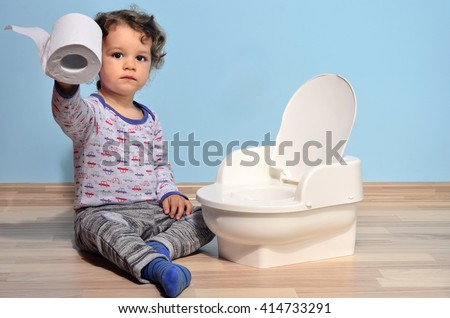 Cute kid potty training for pee and poo.Baby toddler sitting on the floor near a potty and playing with toilet paper