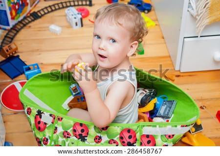 Cute kid sitting in toys box in children room
